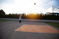 A man, standing tall, preparing to shoot a basketball, in a park stock photos