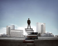 Man standing on the top of books looking the city Royalty Free Stock Photos