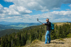 A man standing on the top of high hill with action camera - making selfie, high in mountains. beautiful nature and clouds with blu Royalty Free Stock Image