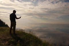 A man standing on top of a hill and looking at his mobile phone in his hands.Silhouette of the traveler. Self royalty free stock photos
