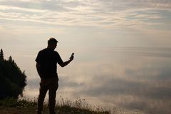 A man standing on top of a hill and looking at his mobile phone in his hands.Silhouette of the traveler. Self stock photos