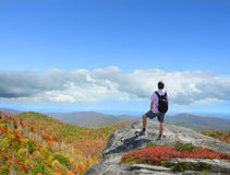 Man standing  on a top of the mountain enjoying mountain view. Stock Image