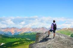 Man standing  on a top of the mountain enjoying mountain view. Stock Photos