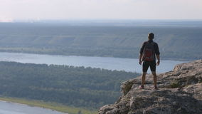 Man standing on top of a mountain with hands raised, Russia . The concept of freedom stock footage