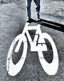 A Man Standing On Top Of A Painted Bicycle Thats Painted On The Ground Royalty Free Stock Images