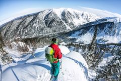 Man standing at top of ridge. Ski touring in mountains. Adventure winter freeride extreme sport.  Stock Image