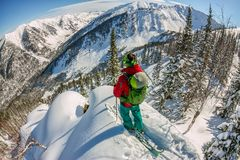 Man standing at top of ridge. Ski touring in mountains. Adventure winter freeride extreme sport.  Royalty Free Stock Image