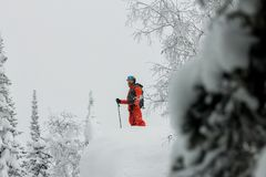 Man standing at top of ridge. Ski touring in mountains. Adventure winter freeride extreme sport.  Stock Photo