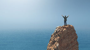 Man standing on top of a rock cliff Royalty Free Stock Images