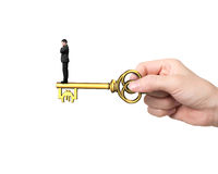 Man standing on treasure key in Euro sign shape. Man standing on treasure key in pound sign shape with hand holding, isolated on white background Royalty Free Stock Photos