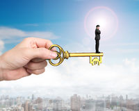 Man standing on treasure key in pound sign shape. Man standing on treasure key in Euro sign shape with hand holding, on sun sky urban scene background Stock Photo
