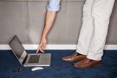 Man standing trying to reach laptop in office Royalty Free Stock Image