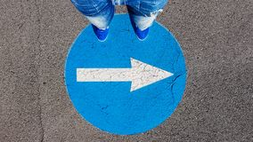Man standing on the turn right traffic road sign symbol with white arrow pointing right stock photos