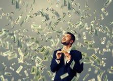 Man standing under dollar's rain Stock Image