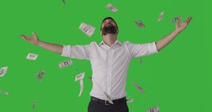 Man standing under raining banknotes over green screen stock video footage