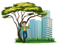 A man standing under the tree across the offices Stock Images