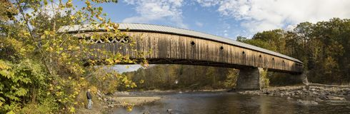 Man standing under wooden covered bridge Stock Images