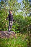 Man standing up on the rock. In the forest Stock Photo
