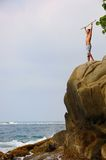Man standing victoriously on a cliff. Man on a rocky cliff at Tayrona Parque in Columbia, with the ocean below Stock Photos