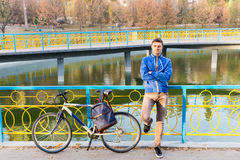 Man standing waiting with his bicycle. Handsome young man standing waiting with his bicycle leaning against colorful railings alongside a canal or lake with Stock Images