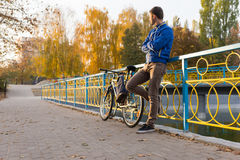 Man standing waiting at a rendezvous. Leaning against colorful metal railings with folded arms and his bicycle alongside him Royalty Free Stock Images
