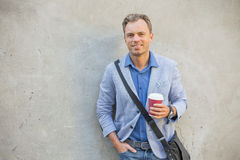 Man standing by the wall with a cup in his hands. Stylish man standing by the wall with a cup in his hands Royalty Free Stock Image