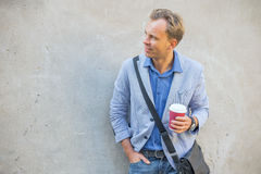 Man standing by the wall. And holding a coffee cup in his hands Stock Image