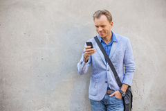 Man standing by the wall and looking at his telephone Royalty Free Stock Image