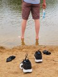 Man standing in water with shoes on the sand. Royalty Free Stock Photography