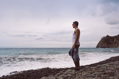Man standing by the waves of the ocean on a rocky beach. Royalty Free Stock Images