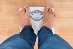 Man Standing On Weighing Scale Royalty Free Stock Image