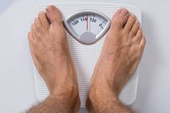Man standing on weight scale. Low section of man standing on weight scale stock photo