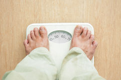 Man standing on weight scales. With bare foot Stock Photography