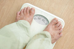 Man standing on weight scales. With bare foot Royalty Free Stock Images