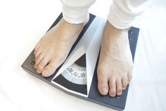Man standing on weight scales Royalty Free Stock Image