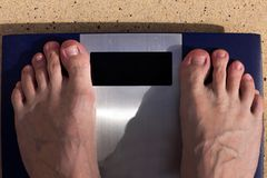 Man standing on weight scales with bare foot. View from top Stock Photo