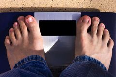 Man standing on weight scales in jeans Stock Photos