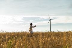 A man standing in a field looking at a wind generator. A man standing in a wheat field looking at a wind generator Royalty Free Stock Photos