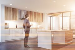 Man standing in white kitchen with bar stock photography