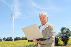 Man standing by wind turbine Stock Photo