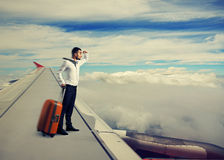 Man standing on the wing. Young businessman standing on the wing of an airplane Stock Photography