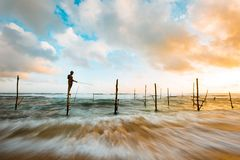 Man Standing in Wood in the Middle of the Ocean While Fishing Under Blue and White Sky during Day Time stock image