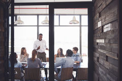 Man stands addressing colleagues at a meeting in a boardroom Stock Photography