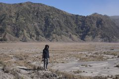 Man Stands Alone in Mount Bromo Caldera. A man stands alone in the Mount Bromo caldera. Active volcanoes in East Java Indonesia with a caldera area of 10 royalty free stock image