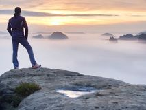 Man stands alone on the peak of rock. Hiker watching to autumn Sun at horizon. Beautiful moment the miracle of nature. Colorful mist in valley. Man hike Stock Images