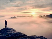 Man stands alone on the peak of rock. Hiker watching to autumn  Sun at horizon. Beautiful moment the miracle of nature. Colorful mist in valley. Man hike Stock Photography