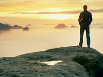 Man stands alone on the peak of rock. Hiker watching to autumn Sun at horizon . Beautiful moment the miracle of nature stock image