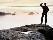 Man stands alone on the peak of rock. Hiker watching to autumn Sun at horizon . royalty free stock photography