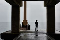 Man stands alone on a pier of sea in bad weather. Foggy air stock photo