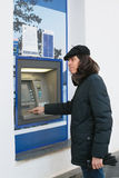 Man stands at ATM for withdrawing cash Stock Photos